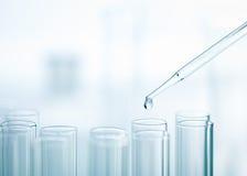 Flüssiger Tropfen von Pipette zu Reagenzglas Lizenzfreie Stockbilder
