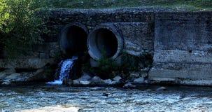 Flüssiges Abwasser fließt heraus in Fluss von den abfliessenden Rohren Stockbild