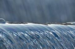 Flüssiges Kaskadenwasser im Nachmittagssonnenlicht Lizenzfreie Stockfotos