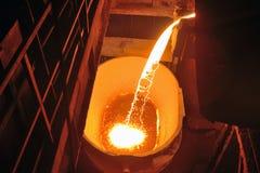 Flüssiges Metall gegossen aus Schöpflöffel stockbild