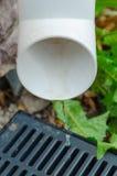 Flüssiges Regenwasser fließt unten in einen dünnen Strom in die Gitterableitung Stockbild