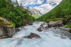 Flüssiges reißender Fluss an den norwegischen Bergen Stockbilder
