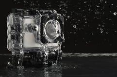Flüssiges Wasser auf der wasserdichten Aktionskamera auf nass schwarzem Steinhintergrund stockfotografie