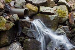 Flüssiges Wasser von einem Rohr unten zu den moosigen Felsen lizenzfreie stockfotos
