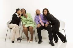 Flüsternde Geschäftsfrauen, während andere heimlich zuhören. Stockfotos