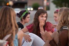 Flüsternde jugendlich Frau mit Freunden Lizenzfreies Stockbild