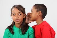 Flüsterndes Geheimnis des Jungen mit zwei Schulefreunden zum Mädchen Stockfoto
