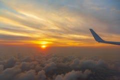 Fl?gel des Flugzeugs auf dem Wolkenmeersonnenuntergang-Himmelhintergrund vom Fensterflugzeug lizenzfreie stockbilder