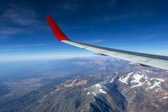 Fl?gel eines Flugzeugfliegens ?ber den Morgenwolken und dem Andengebirgszug lizenzfreies stockfoto