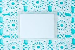 Flach, gelegt, ein Blatt Papier für Text auf einen blauen Hintergrund mit gewirkter weißer Weinlesespitze, Winterthema, quadratis stockfoto