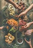 Flach-Lage von Freunden übergibt zusammen essen und trinken stockbilder