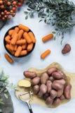 Flache gelegte Kartoffeln auf Schneidebrett und Karotten in der Schüssel stockfoto