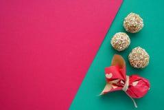 Flache gelegte runde Süßigkeiten der handgemachten Kokosnuss auf dem Grün und dem Rosa stiegen rosiger Hintergrund mit Herzen am  lizenzfreies stockbild