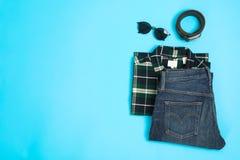 Flache gelegte Zusammensetzung mit Hemd, Jeans, Gläsern und Gurt lizenzfreie stockbilder