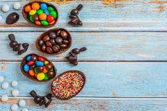 Flache gelegte Zusammensetzung mit Schokoladen-Ostereiern, Kaninchen und Bonbons auf blauem hölzernem Hintergrund Beschneidungspf lizenzfreies stockbild