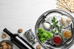 Flache gelegte Zusammensetzung mit symbolischen Passahfest Pesach-Einzelteilen und Mahlzeit auf hölzernem Hintergrund stockfotografie