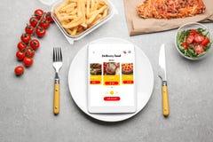 Flache gelegte Zusammensetzung mit Tablet-Computer und zum Mitnehmen Mahlzeiten auf grauem Hintergrund Lebensmittellieferung stockbild