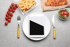 Flache gelegte Zusammensetzung mit Tablet-Computer und zum Mitnehmen Mahlzeiten auf grauem Hintergrund Lebensmittellieferung lizenzfreie stockbilder