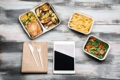 Flache gelegte Zusammensetzung mit Tablet-Computer und zum Mitnehmen Mahlzeiten auf hölzernem Hintergrund Lebensmittellieferung stockbild