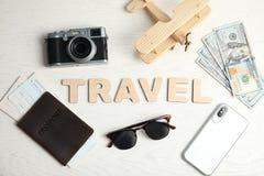 Flache gelegte Zusammensetzung mit Wort REISE, Kamera und Pass auf hölzernem Hintergrund lizenzfreie stockfotografie