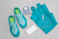 Flache hellblaue Turnschuhe, eine Flasche Wasser, ein T-Shirt und Kopfhörer auf einem grauen konkreten Hintergrund Das Konzept ei Stockfoto