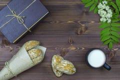 Flache Lage Auf dem Tisch blüht Frühling, ein Becher mit Milch und süße selbst gemachte Plätzchen und Bücher lizenzfreies stockfoto