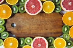 Flache Lage Beschneidungspfad eingeschlossen Hölzernes Brett in der Mitte mit geschnittener Kiwi, Orange, Pampelmuse und Mandarin lizenzfreies stockfoto