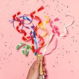 Flache Lage der Feier Sektflasche mit bunten Parteiausläufern auf rosa Hintergrund Flache Lage der Feier Champagne-bott Lizenzfreie Stockbilder
