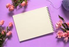 Flache Lage der romantischen Rosen mit Leerseitennotizbuch auf violettem Hintergrund Lizenzfreies Stockfoto