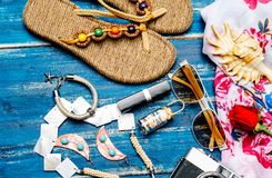 Flache Lage der Sommermode mit Kamerapantoffelsonnenbrille und anderem Mädchenzubehör auf blauem Hintergrund Stockfotos