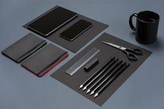 Flache Lage des leeren schwarzen Papierblattes, der schwarzen Briefpapiereinzelteile und der Kaffeetasse auf dem grauen Desktop S Stockfoto