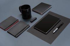 Flache Lage des leeren schwarzen Papierblattes, der schwarzen Briefpapiereinzelteile und der Kaffeetasse auf dem grauen Desktop S Stockbilder