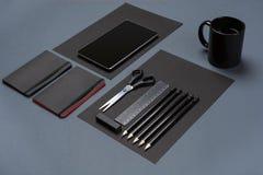 Flache Lage des leeren schwarzen Papierblattes, der schwarzen Briefpapiereinzelteile und der Kaffeetasse auf dem grauen Desktop S Stockfotos