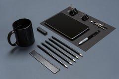 Flache Lage des leeren schwarzen Papierblattes, der schwarzen Briefpapiereinzelteile und der Kaffeetasse auf dem grauen Desktop S Stockbild
