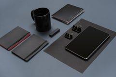 Flache Lage des leeren schwarzen Papierblattes, der schwarzen Briefpapiereinzelteile und der Kaffeetasse auf dem grauen Desktop S Stockfotografie
