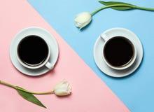 Flache Lage des minimalistic Bildes von zwei Tasse Kaffees und von Tulpen auf rosa und gelbem Hintergrund Minimalismuskaffeekonze Stockbild