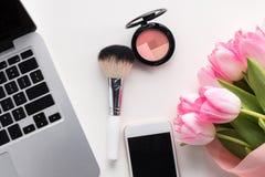 Flache Lage des offenen Laptops, des Smartphone mit leerem Bildschirm, der Blumen und der Make-upbürste Stockbilder