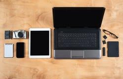 Flache Lage des persönlichen Bürozubehörs, des Laptops, des Notizbuches, der Kaffeetasse und der Kamera auf hölzernem Hintergrund Lizenzfreie Stockfotografie