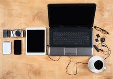 Flache Lage des persönlichen Bürozubehörs, des Laptops, des Notizbuches, der Kaffeetasse und der Kamera auf hölzernem Hintergrund Stockfoto