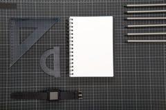Flache Lage des schwarzen Büroartikels, des Notizblockes, des smartwatch und der Bleistifte Lizenzfreie Stockfotografie