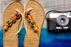 Flache Lage des Sommergegenstandes mit Kamera und der Pantoffel auf die Tasche als Hintergrund Stockbilder