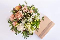 Flache Lage eines schönen Blumenstraußes mit Notizbuch auf dem weißen Hintergrund stockbilder
