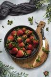 Flache Lage, Erdbeeren auf Schwarzblech, hölzernes Schneidebrett stockfotografie