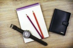 Flache Lage Männer ` s Armbanduhr, Notizblock, zwei Bleistifte und eine Männer ` s Geldbörse liegen auf der Beschaffenheit des Ho Lizenzfreie Stockfotos