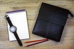 Flache Lage Männer ` s Armbanduhr, Notizblock, zwei Bleistifte und eine Männer ` s Tasche liegen auf der Beschaffenheit des Holze Stockbilder