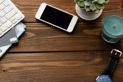 Flache Lage mit Arbeitsplatz auf Holztisch backgroud Tastatur, Blatt von monstera Anlage, Handy, Kreditbankkarte, Banknote von 2 Stockfoto