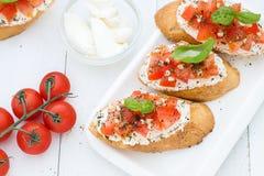 Flache Lage mit bruschettas mit Sahne Käse, Tomaten und Basilikum Beschneidungspfad eingeschlossen Stockfotografie