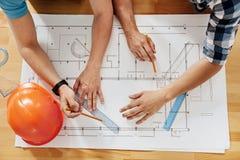 Flache Lage mit den männlichen Händen, die einen Plan herstellen Lizenzfreie Stockfotos