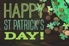 Flache Lage mit grünem Hut, Münzen und Shamrocks auf Holzoberfläche mit glücklichem St.-patricks Tag lizenzfreie stockfotografie