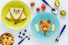 Flache Lage mit kreativ angeredetem Kind-` s Frühstück mit Beeren und Kiwi lizenzfreies stockfoto